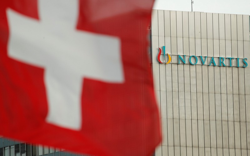 FILE PHOTO: Switzerland's national flag flies in front of the logo of Swiss drugmaker Novartis in Basel