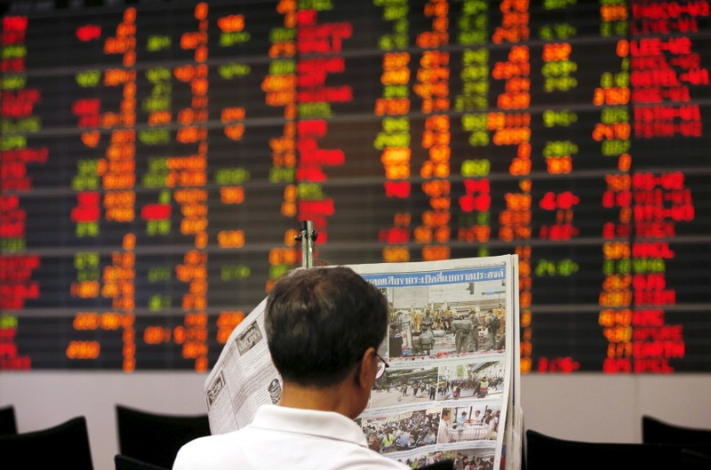 A Thai investor reads a newspaper in front of an electronic board displaying live market data at a stock broker's office in central Bangkok