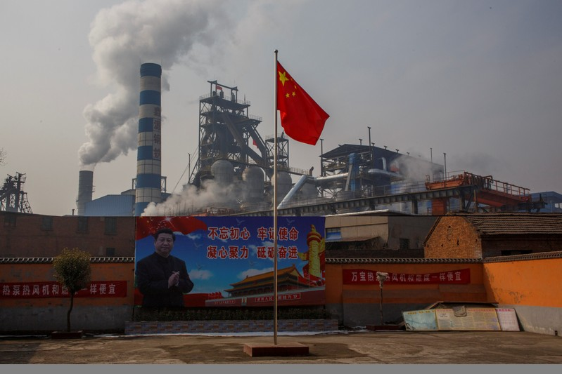 FILE PHOTO: A poster showing Chinese President Xi Jinping is seen in front of the Xinyuan Steel plant in Anyang