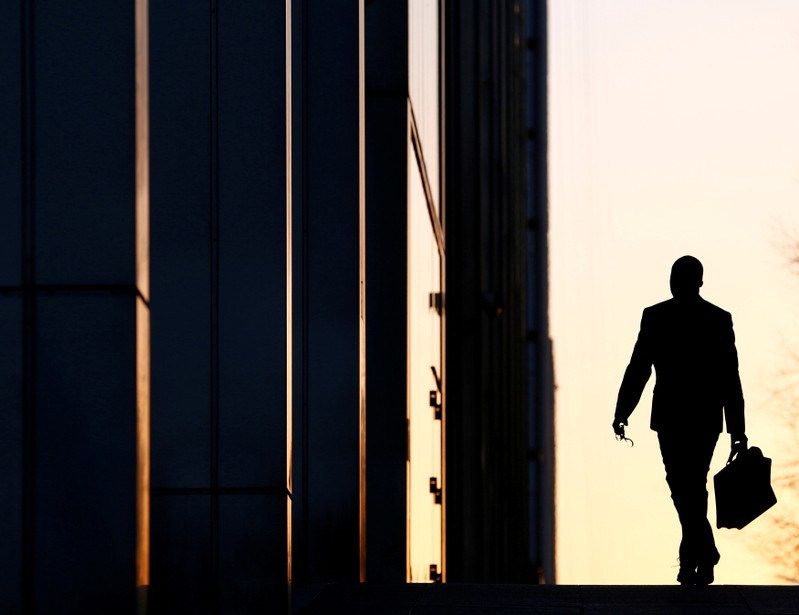 FILE PHOTO - A worker arrives at his office in the Canary Wharf business district in London