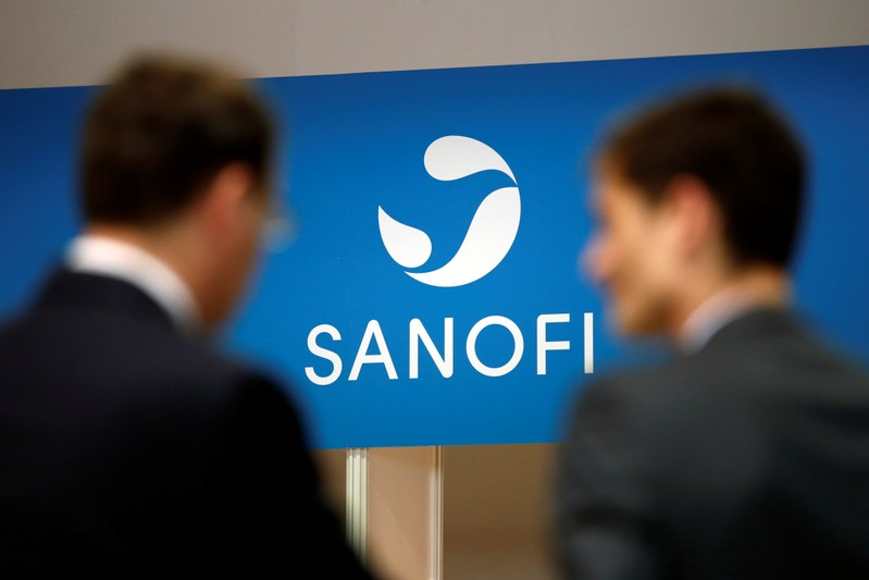 Shareholders talk in front of a logo of Sanofi during the company's shareholders meeting in Paris
