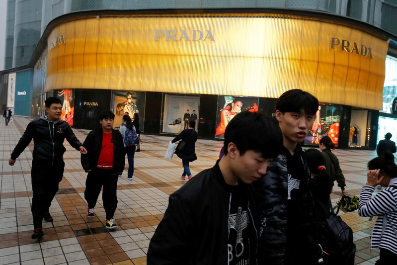 FILE PHOTO: People walk past a Prada luxury fashion boutique near Wangfujing Street
