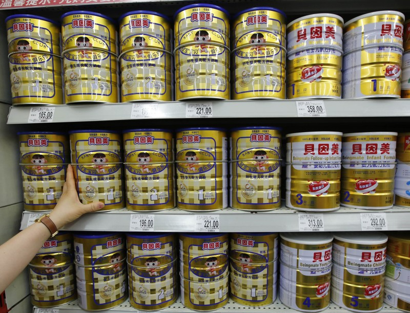A woman chooses Beingmate's milk powder products at a supermarket in Beijing