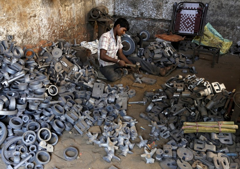 A worker separates casting joints of gearboxes inside a small-scale automobile manufacturing unit in Ahmedabad
