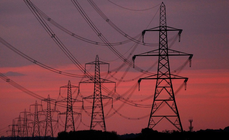 FILE PHOTO: The sun rises behind electricity pylons near Chester, northern England