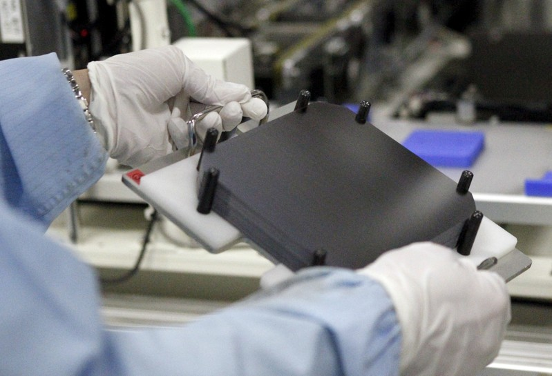 A worker works along the production line of the solar cell at Shap Corp's Sakai plant in Sakai, western Japan