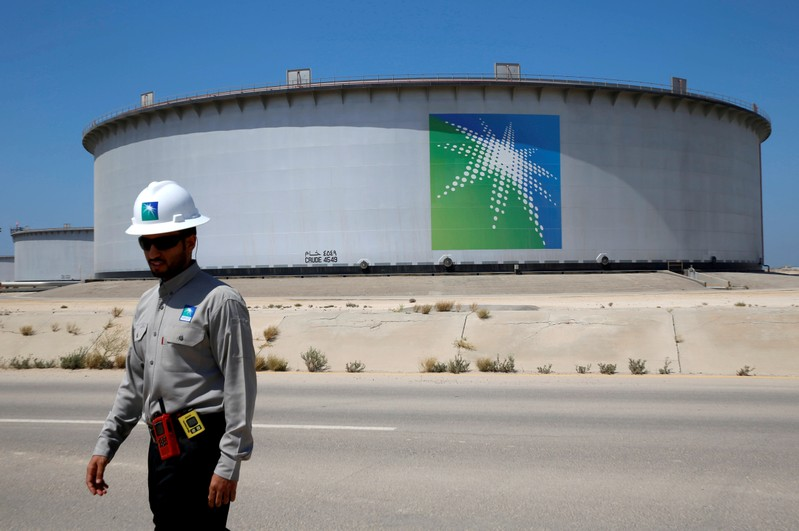 FILE PHOTO: An Aramco employee walks near an oil tank at Saudi Aramco's Ras Tanura oil refinery and oil terminal