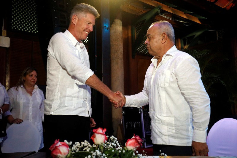 David Cutter, President of Global Supply and Procurement of British beverage giant Diageo, and Juan Gonzalez Escalona, President of the state-run Cuba Ron, shake hands after signing a joint venture to market Santiago de Cuba rum, in Havana