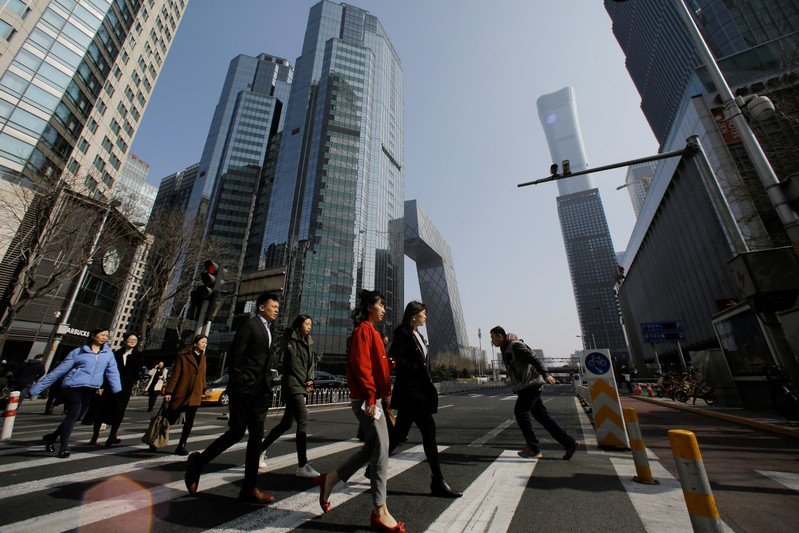 FILE PHOTO: People cross a street in the Central Business District (CBD) one day before the opening session of the National People's Congress (NPC) in Beijing
