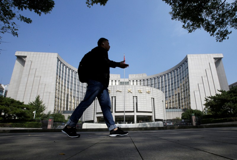 A man walks past the headquarters of the PBOC, the central bank, in Beijing