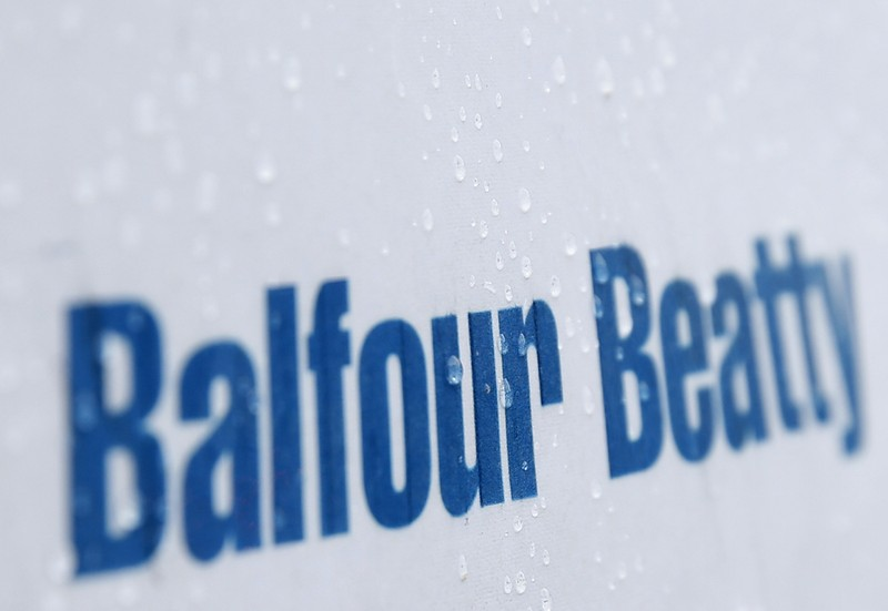 Raindrops are seen on a sign at a Balfour Beatty construction site in central London