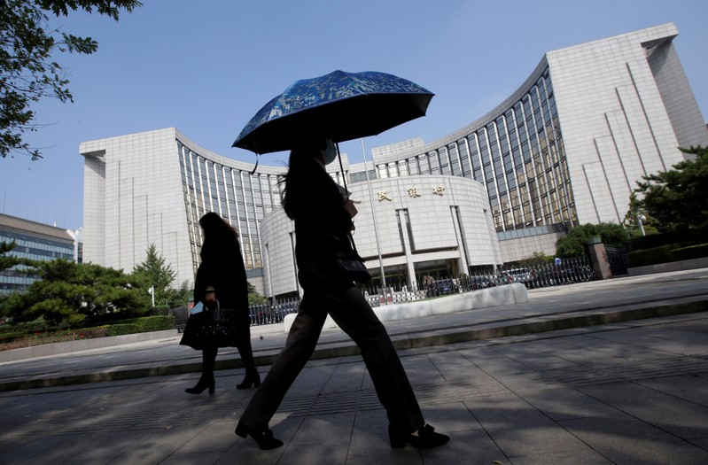 People walk past the headquarters of the PBOC, the central bank, in Beijing