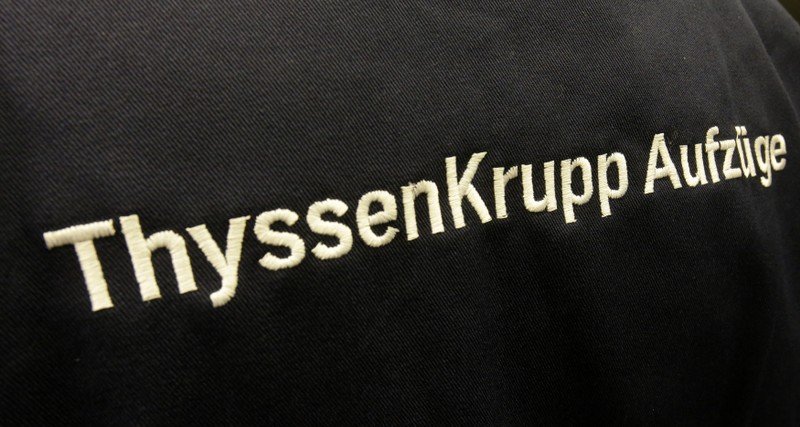 Logo of ThyssenKrupp AG elevator section is pictured at working clothes of company service engineer in Berlin