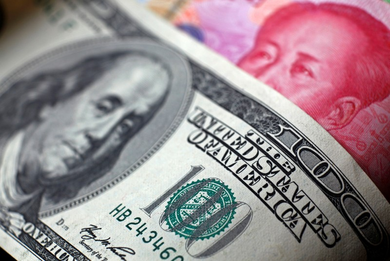 FILE PHOTO: FILE PHOTO: File photo of a Chinese 100 yuan banknote being placed under a $100 banknote in this photo illustration taken in Beijing