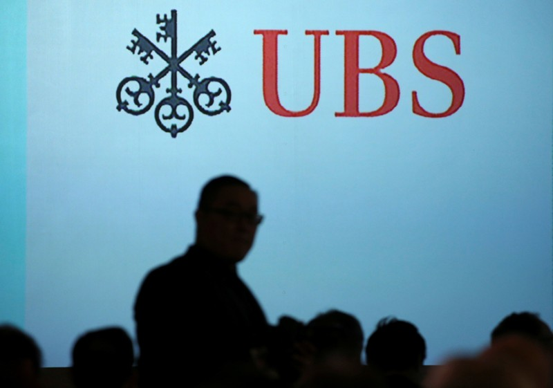 A man walks past a UBS logo projected on a screen in Singapore