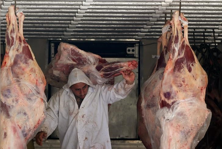 A butcher unloads beef from a truck outside a butcher's shop in Sao Paulo
