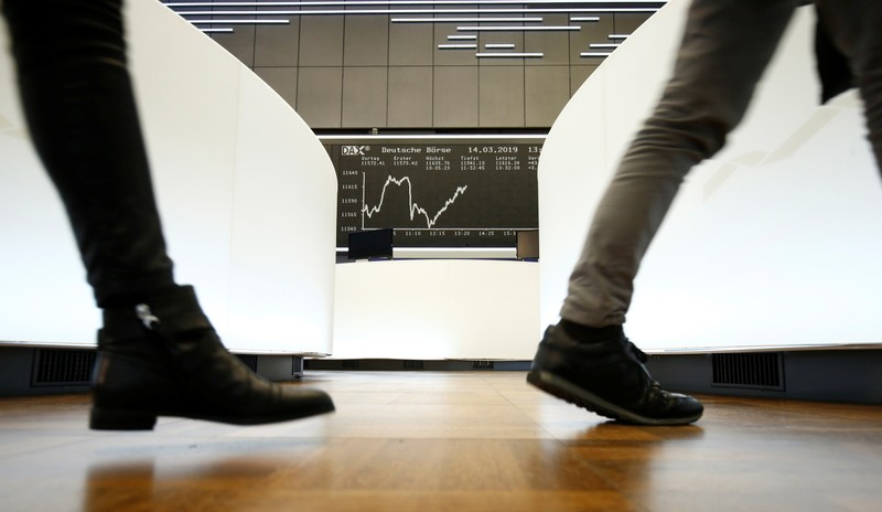 Traders walk past the German share price index DAX graph at Frankfurt's stock exchange in Frankfurt