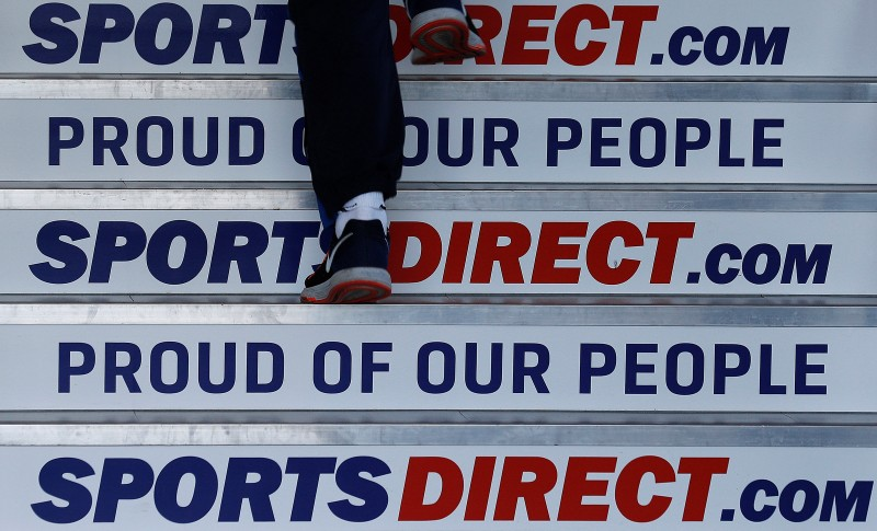 FILE PHOTO: A worker walks up stairs before a Sports Direct general meeting to vote on the re-appointment of chairman Keith Hellawell in Shirebrook