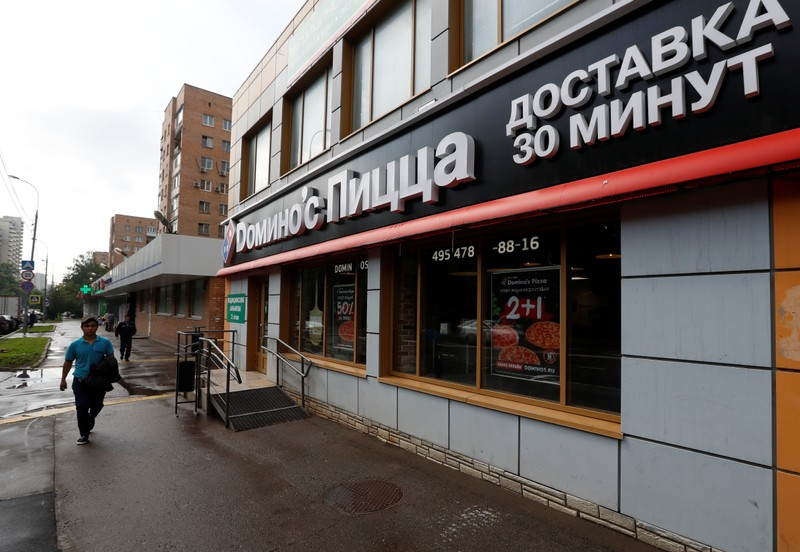A man walks past a Domino's Pizza restaurant in Moscow