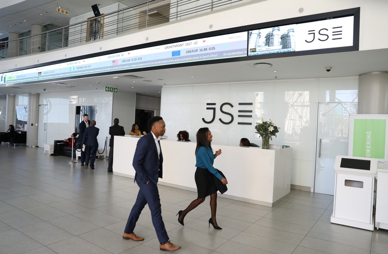 Visitors walk past a reception with an electronic board displaying movements in major indices at the Johannesburg Stock Exchange building in Sandton, Johannesburg
