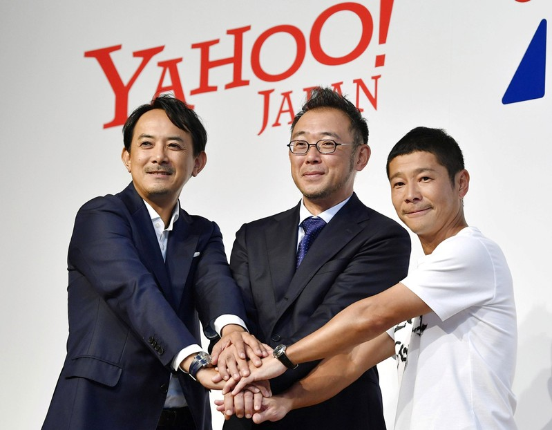 Founder of Zozo Inc. Yusaku Maezawa poses for a photo with his successor Kotaro Sawada and Yahoo Japan CEO Kentaro Kawabe during a news conference in Tokyo
