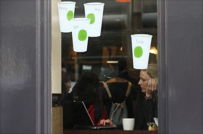 FILE PHOTO:  A woman looks at a laptop while sitting in a Starbucks in London