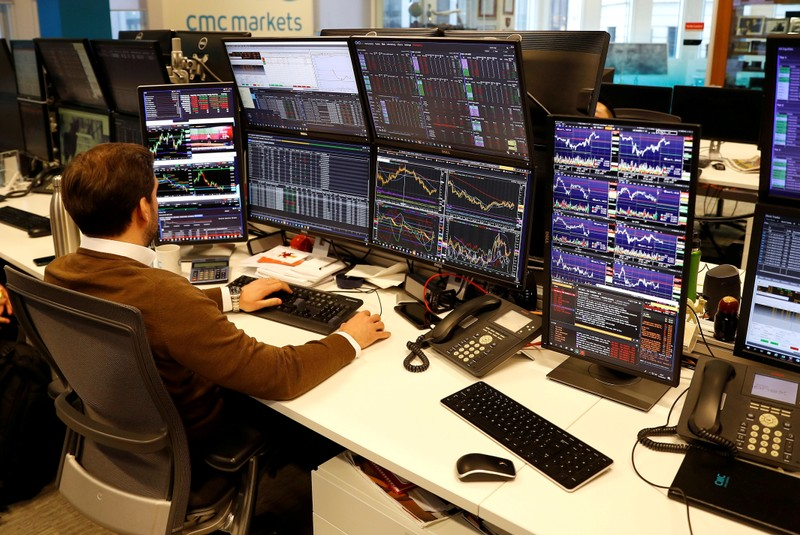 FILE PHOTO: A financial trader works at his desk at CMC Markets in the City of London, Britain