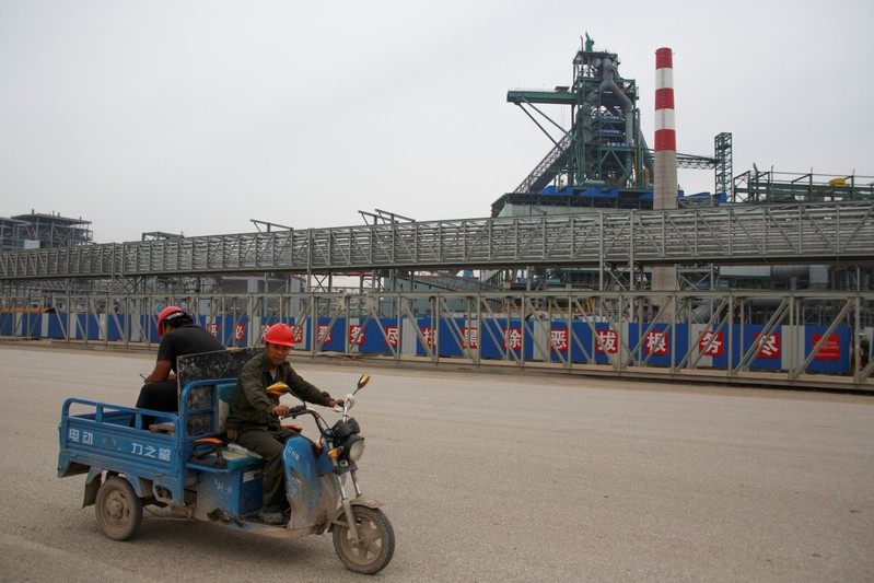 Workers drive past the Hebei Zongheng Iron and Steel plant that is under construction at the Tangshan Fengnan Economic Development Zone