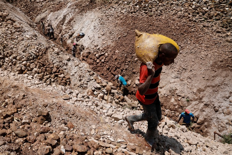 A man carries sacks of ore at the SMB coltan mine near the town of Rubaya