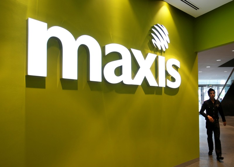 FILE PHOTO: A customer walks past a logo of Malaysian mobile network operator Maxis at its headquarters in Kuala Lumpur