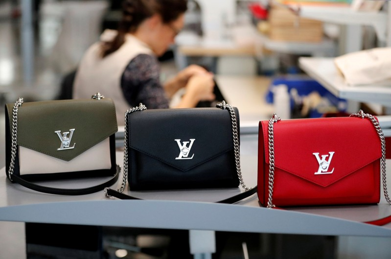 FILE PHOTO: Louis Vuitton handbags are displayed as an employee works in a Vuitton new high-end garment factory in Beaulieu-sur-Layon