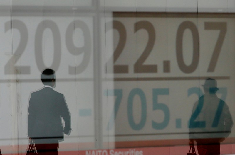 Men are reflected on an electronic board showing the Nikkei stock index outside a brokerage in Tokyo