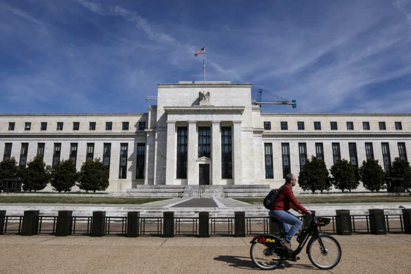 FILE PHOTO: A man rides a bike in front of the Federal Reserve Board building on Constitution Avenue in Washington