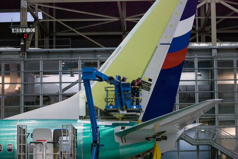 Boeing employees work on the tail of a Boeing 737 NG at the Boeing plant in Renton, Washington