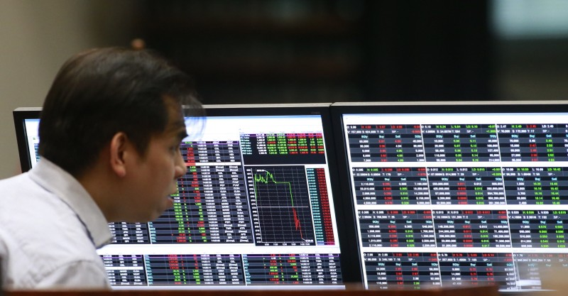 A stockbroker looks on his monitors inside the Philippine Stock Exchange (PSE) in Makati city, metro Manila