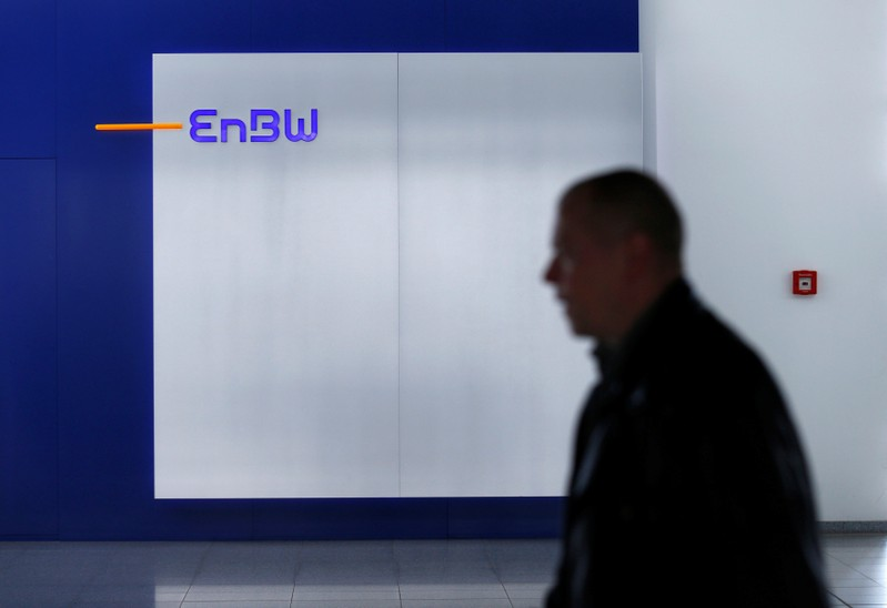 A man walks past a logo of German power supplier EnBW Energie Baden-Wuertemberg AG in the companies headquarters in Karlsruhe