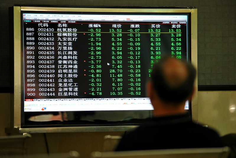 Man sits in front of a screen displaying stock information at a brokerage house in Jinhua