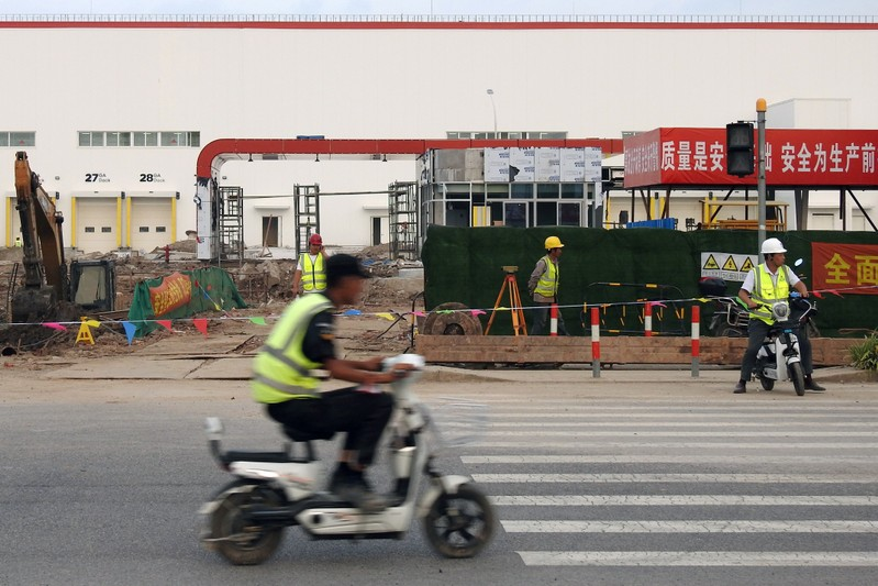 FILE PHOTO: Workers are seen outside a planned entrance of U.S. electric carmaker Tesla's Gigafactory that is under construction in Shanghai