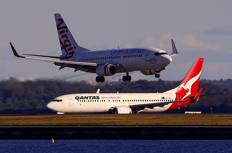 A Qantas Airways Boeing 737 plane sits on the tarmac as a Virgin Australia Boeing 737 plane lands at Sydney's Mascot Airport