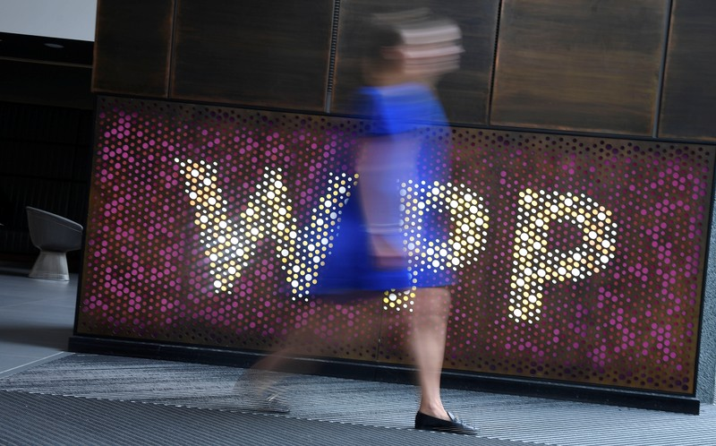 A woman walks past signage for WPP Group, the largest global advertising and public relations agency at their offices in London