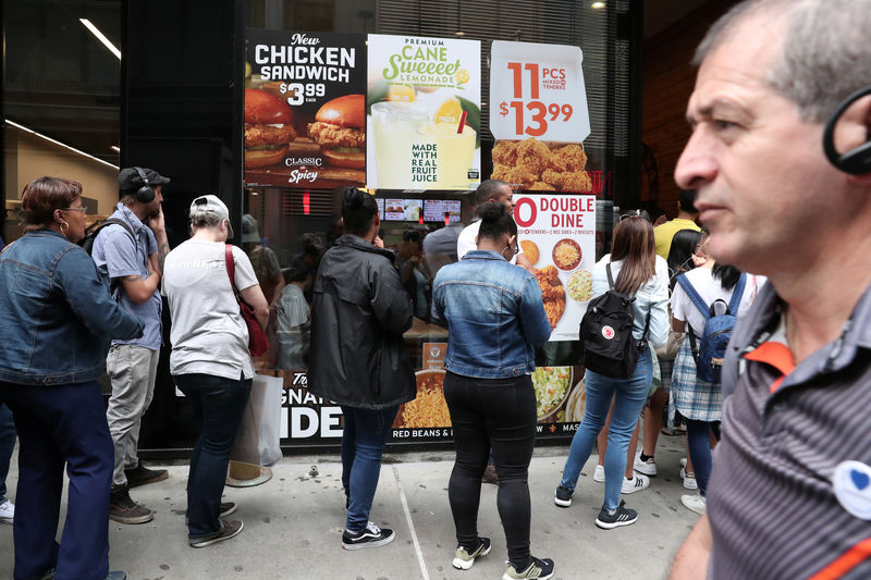 People wait in line outside a Popeyes Louisiana Kitchen restaurant in New York City, New York