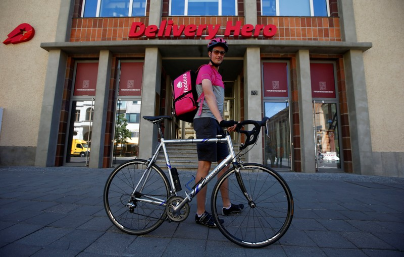 A Foodora delivery cyclist poses in front of Delivery Hero headquarters in Berlin