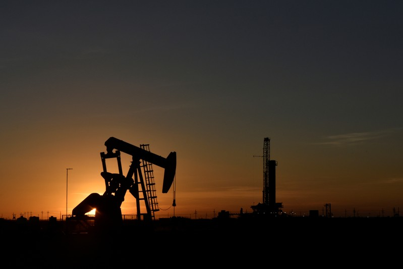 A pump jack operates in front of a drilling rig at sunset in an oil field in Midland
