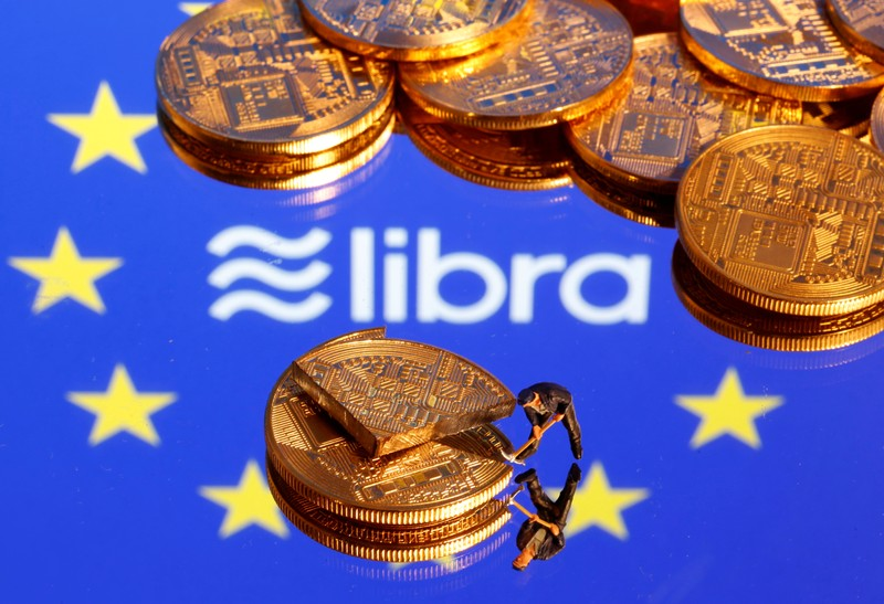 A small toy figure is seen on representations of the virtual currency on a displayed European Union flag and the Facebook Libra logo in this illustration picture