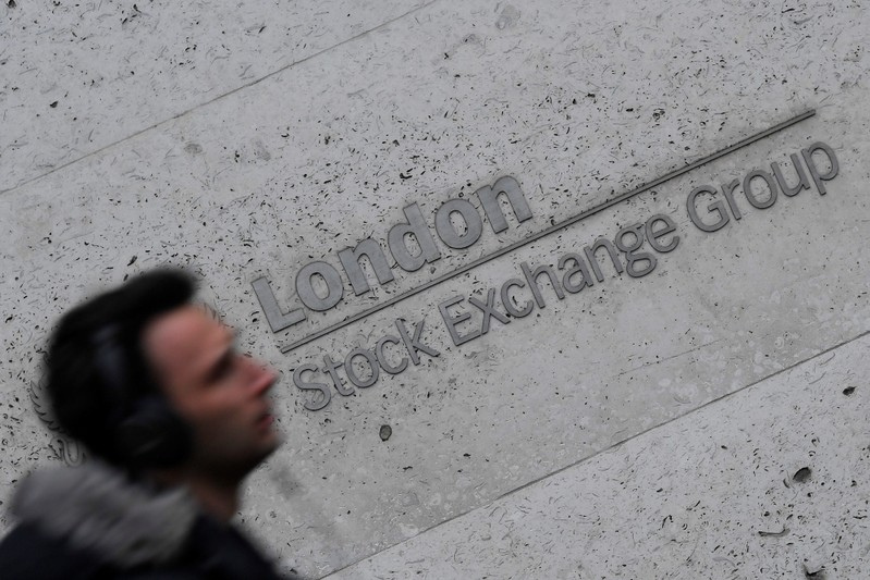 FILE PHOTO: A man walks past the London Stock Exchange Group offices in the City of London, Britain