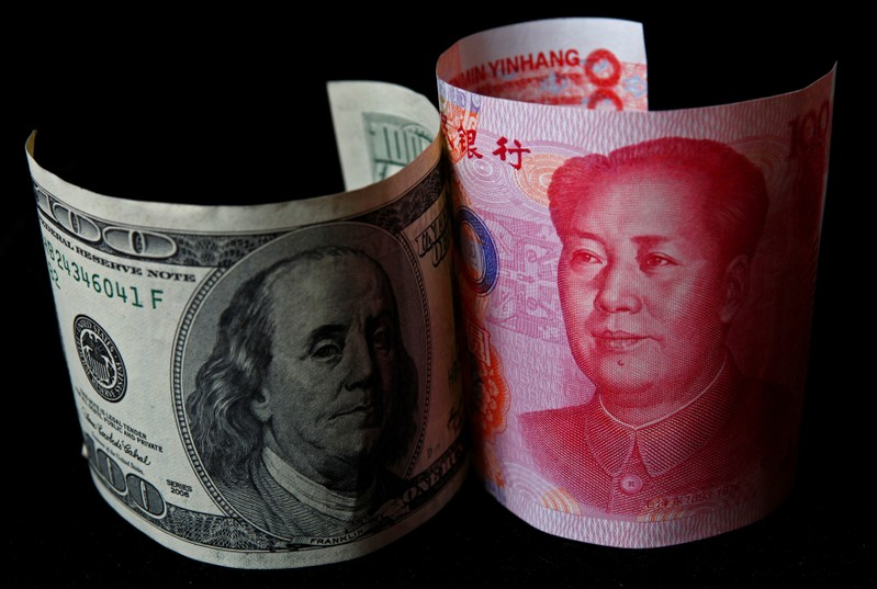 FILE PHOTO: A 100 yuan banknote is placed next to a $100 banknote in this picture illustration taken in Beijing