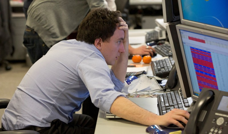 FILE PHOTO: A trader looks at his screen on the IG Group trading floor in London