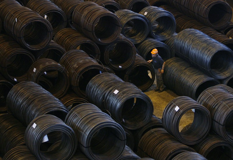 A labourer walks past rolled steel coils at the factory of Swiss Steel AG which is partly owned by the 'Schmolz + Bickenbach' group in Emmenbruecke, outside Lucerne