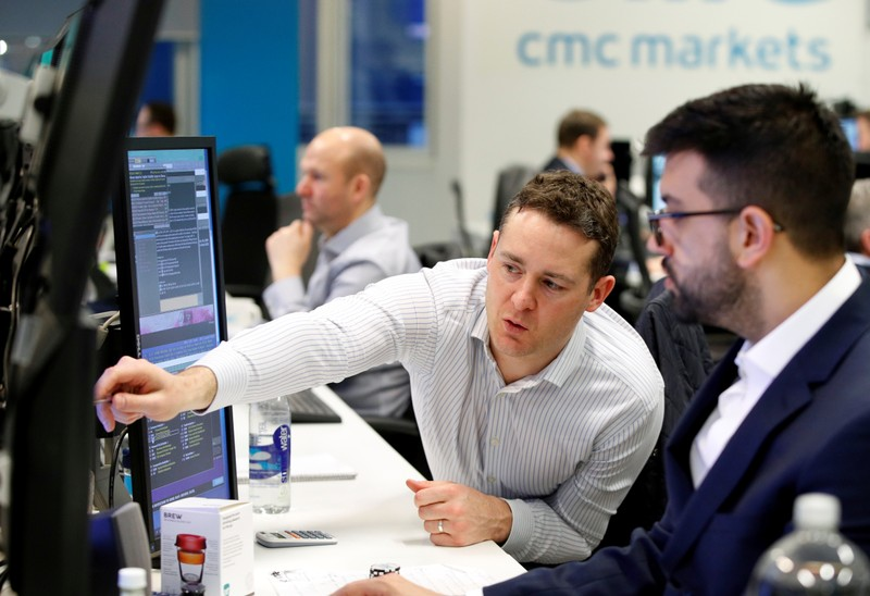Traders work at their desks at CMC Markets in London