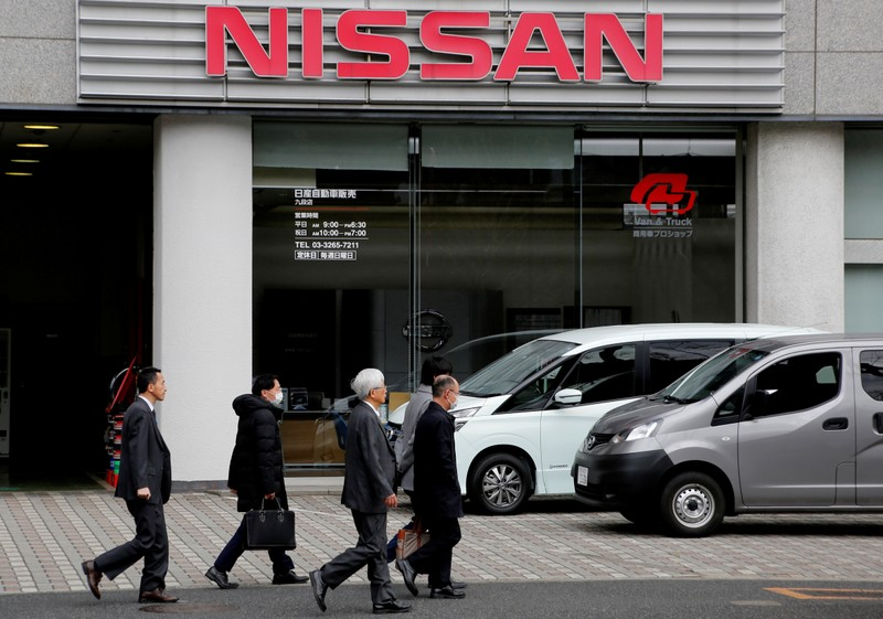 People walk past a dealer shop of Nissan Motor Co. in Tokyo